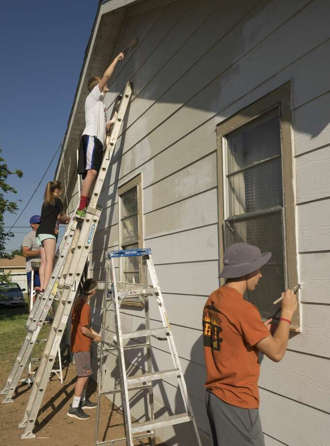 Students from Midland Christian work 04-19-17 on painting a home as part of Christmas in Action at a home in the 600 block of S. Benton. Tim Fischer/Reporter-Telegram Photo: Tim Fischer/Midland Reporter-Telegram