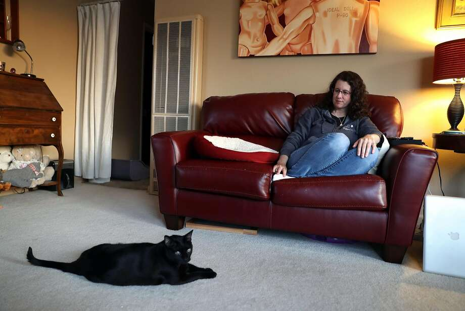 Amy Tucker relaxes with her cat, Dipper, at her apartment in Pacifica, Calif., on Tuesday, April 18, 2017. Tucker is facing a $300 rent increase since April 1. After a contentious meeting last week, the Pacifica City Council voted 3-2 to approve a temporary rent- and eviction-control ordinance. Photo: Scott Strazzante, The Chronicle