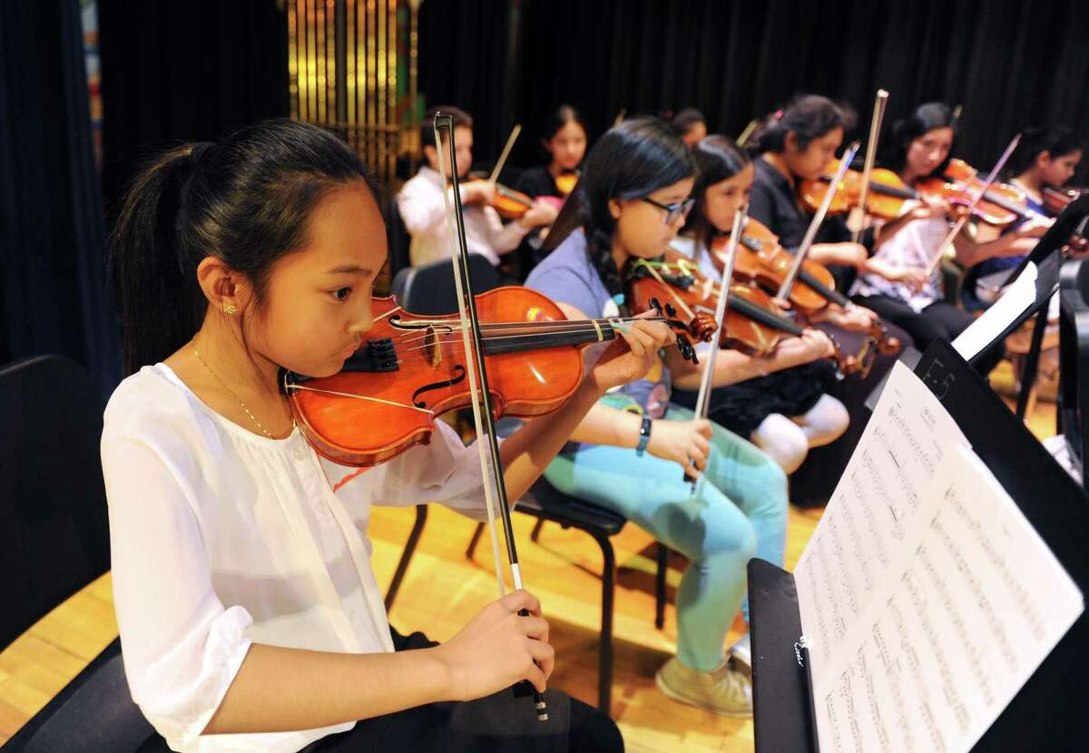 """Hamilton Avenue School fifth-grader Kristine DeJesus practices """"Ode to Joy"""" at the Tuning Into Music master class at Western Middle School in Greenwich, Conn. Tuesday, April 18, 2017. Members of the Greenwich Symphony Orchestra provided a free music lesson to students in grades four through 12 who could not otherwise afford additional musical training. Students broke down into groups by instrument and the lesson culminated with a group performance of """"Ode to Joy."""""""