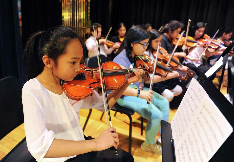 "Hamilton Avenue School fifth-grader Kristine DeJesus practices ""Ode to Joy"" at the Tuning Into Music master class at Western Middle School in Greenwich, Conn. Tuesday, April 18, 2017. Members of the Greenwich Symphony Orchestra provided a free music lesson to students in grades four through 12 who could not otherwise afford additional musical training. Students broke down into groups by instrument and the lesson culminated with a group performance of ""Ode to Joy."" Photo: Tyler Sizemore / Hearst Connecticut Media / Greenwich Time"