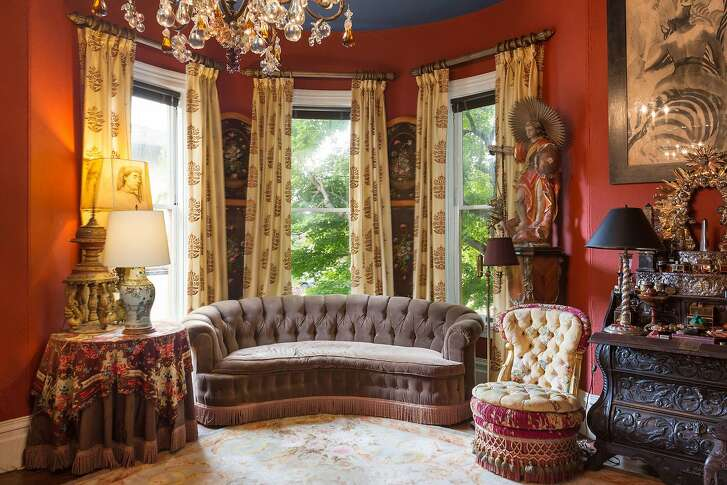 The living room hosts bay windows overlooking the street.