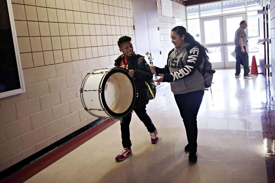 Brenten Williams (left), 12, holds a bass drum after rehearsal while putting it away as Sahara Ahmed asks if she can carry it. Photo: Lea Suzuki, The Chronicle