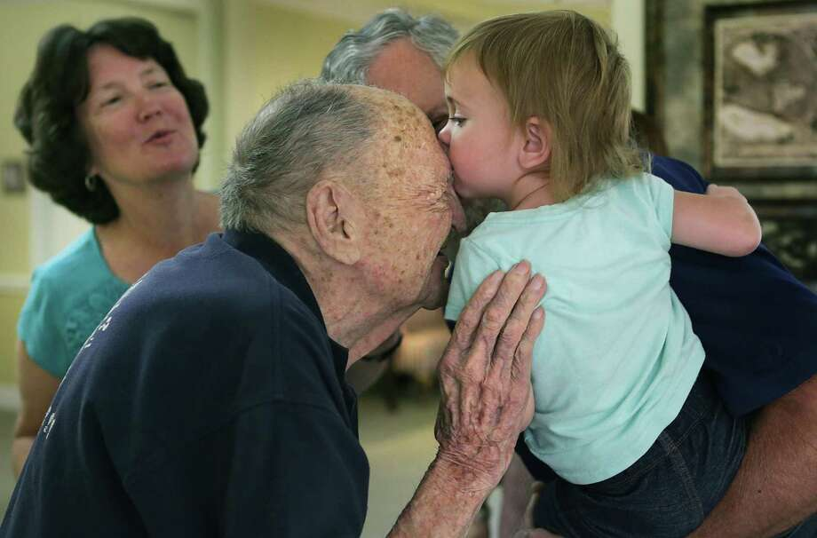 Eugene Ruf, a veteran of World War II, gets a kiss from his 22 month-old great grand daughter Grace Friedeck who is held by her grandfather Stanley Friedeck and grand mother Eileen Friedeck, left, celebrating his 108th birthday on Wednesday, April 19, 2017, at Brookdale Senior Living Solutions. Photo: Bob Owen, Staff / San Antonio Express-News / ©2017 San Antonio Express-News