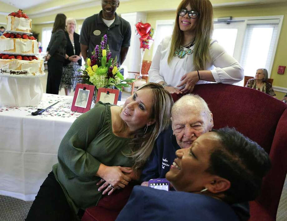 Ruf leans in to give Cynthina Williams (right) a kiss as they pose with Brenda Sanchez (left) at Brookdale. Ruf fought as a combat engineer in the Allied approach to the Siegfried Line in the Europe in World War II and went back to war in Korea after 1950. Photo: Bob Owen /San Antonio Express-News / ©2017 San Antonio Express-News