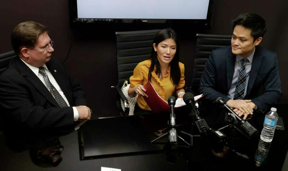 Attorneys David Armbruster, left, and Brian Nguyen, right, listen as Tu Thien Huynh speaks. She had been charged with murdering her husband but the charges have been dropped after the death was ruled a suicide. Photo: Melissa Phillip, Staff / © 2017 Houston Chronicle