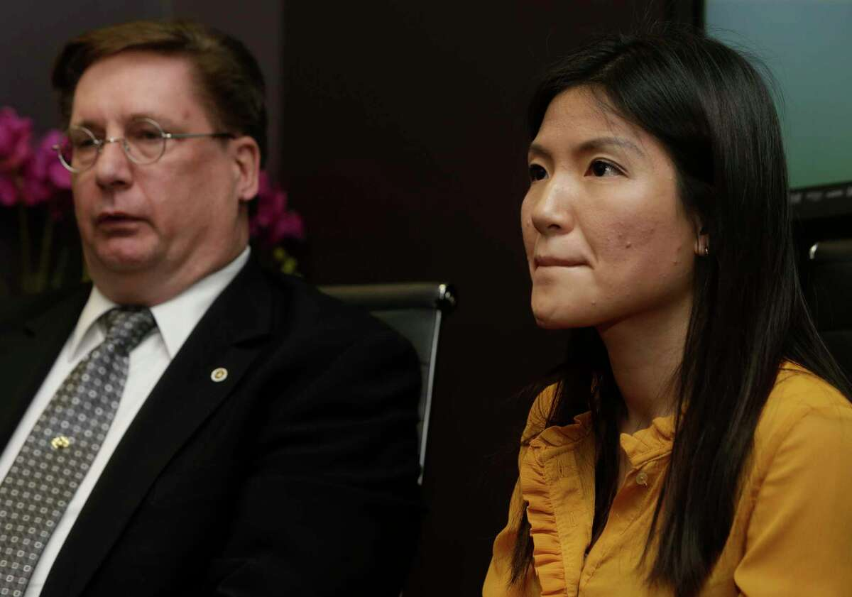 Attorney David Armbruster, left, and Tu Thien Huynh are shown at a news conference Wednesday. She had been charged with murdering her husband, Steven Hafer, but the charges have been dropped and her husband's death has been ruled a suicide.)