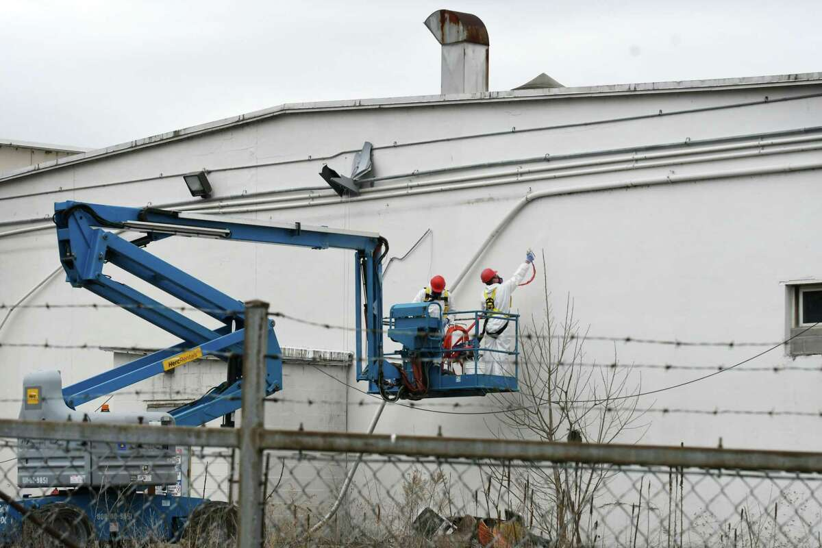EPA contractors spray the exterior of a north-facing building at the former Beech-Nut plant with a protective encapsulating spray on Wednesday, April 19, 2017, in Canajoharie, N.Y. EPA tests found unsafe levels of asbestos in piles of demolition debris and on portions of the exterior and interior of the former food plant. (Will Waldron/Times Union)