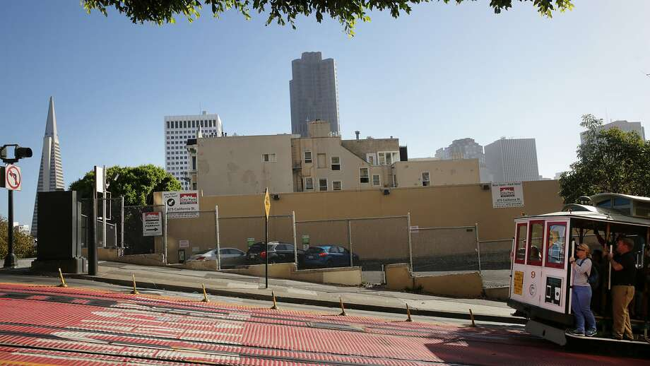 A cable car passes in front of a lot and neighboring parking garage at the intersection of Powell and California Streets on Thursday, October 22,  2015 in San Francisco, Calif.  A developer has a proposal to build a six story condo building on the corner which would replace the lot and parking garage. Photo: Lea Suzuki, The Chronicle