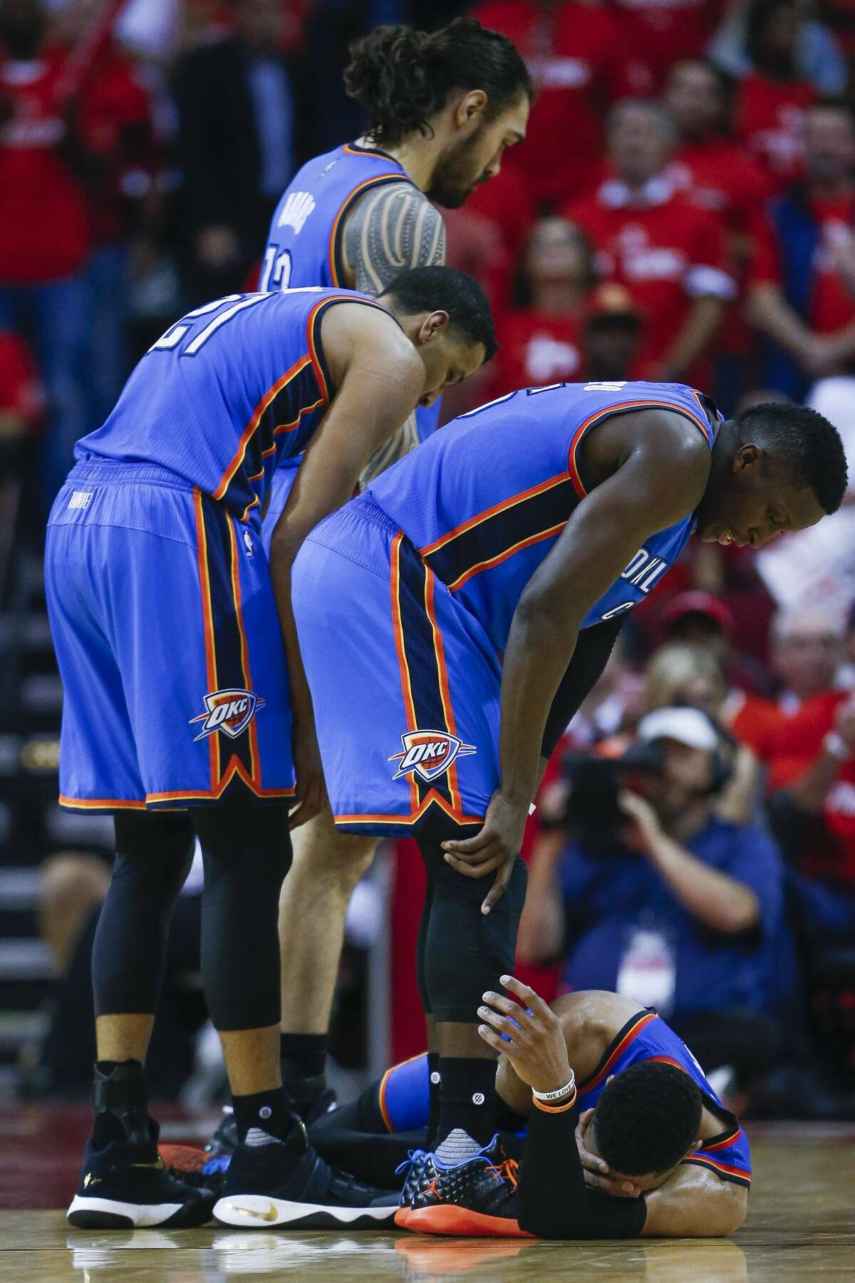 Oklahoma City Thunder teammates surround Oklahoma City Thunder guard Russell Westbrook (0) as he lays on the court after a foul as the Houston Rockets beat the Oklahoma City Thunder 115-111 in Game 2 of the first-round playoff series Wednesday, April 19, 2017 in Houston at the Toyota Center. ( Michael Ciaglo / Houston Chronicle)