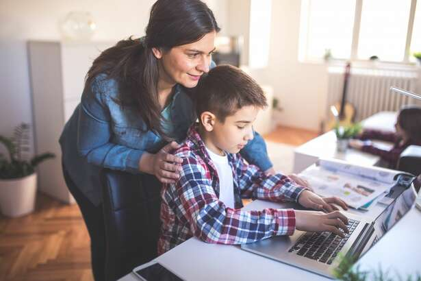 Mother helps son how to use a lap top and internet