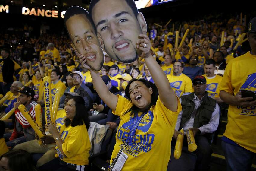 FILE - Warriors fan Dee Pangan dances with a cutout of Stephen Curry and Klay Thompson during the second half of the NBA playoffs, Round 1, Game 2, between the Golden State Warriors and Portland Trail Blazers at Oracle Arena in Oakland in this file photo from Wednesday, April 19, 2017. The Warriors' fans endured five seasons of poor performance before this era of dominance began.