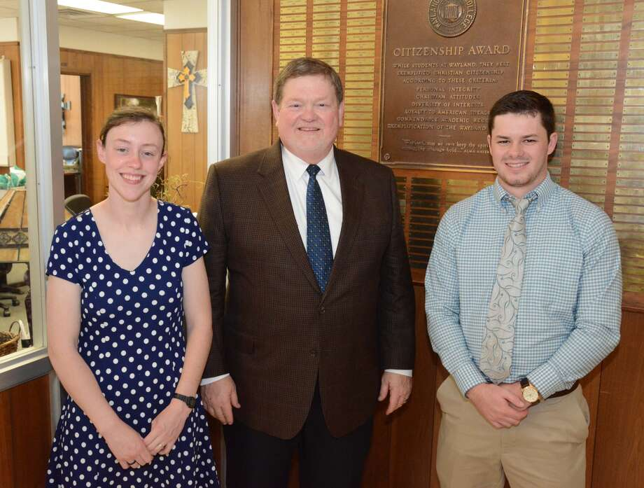 The 2017 Wayland Citizenship Award winners Rachel Bohnet (left) and Tyler Seward (right) stand with WBU President Dr. Bobby Hall after affixing a plate engraved with each of their names to the Citizenship Award plaque hanging in Gates Hall. The Citizenship Award is the highest honor given to students by the university.