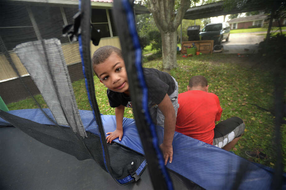 Charlie Janeux and his brother Jason Janeaux finish jumping on the trampoline at their family's Nederland home on Monday. Doctors told Charlie's mom that he would likely never walk after his father crushed parts of his skull when he was 22 days old. Photo taken Monday, April 17, 2017 Guiseppe Barranco/The Enterprise Photo: Guiseppe Barranco, Guiseppe Barranco/The Enterprise