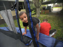 Charlie Janeux and his brother Jason Janeaux finish jumping on the trampoline at their family's Nederland home on Monday. Doctors told Charlie's mom that he would likely never walk after his father crushed parts of his skull when he was 22 days old. Photo taken Monday, April 17, 2017 Guiseppe Barranco/The Enterprise