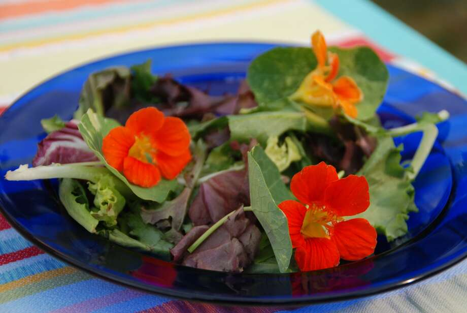 Add a bit of color and interest to salads with edible flowers like nasturtium. Photo: Melinda Myers