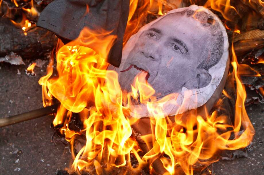 """NEW DELHI, INDIA - JANUARY 24: Effigy with a portrait of U.S. President Barack Obama burns on a road during a protest march by various Left Front political parties against his visit to India, on January 24, 2015 in New Delhi, India. According to party sources, the Left parties had decided to hold protests against US """"imperialism"""" and """"military interventions"""" in other countries and none of its leaders would be attending the dinner. (Photo By Virendra Singh Gosain/Hindustan Times via Getty Images) Photo: Hindustan Times/Hindustan Times Via Getty Images"""