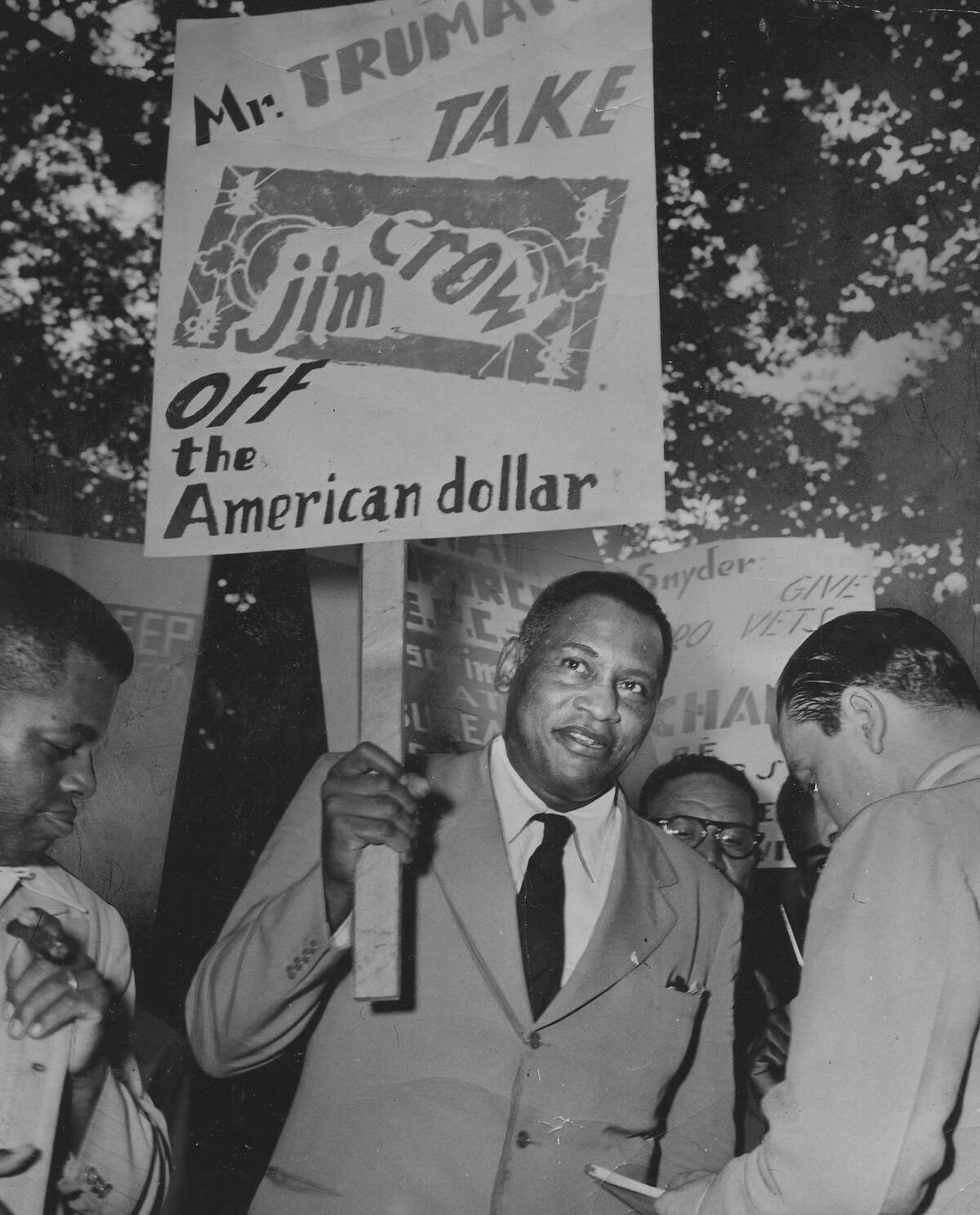 Paul Robeson, actor and singer, in a protest march outside the White House, with a banner requesting that President Truman take Jim Crow off the American dollar.