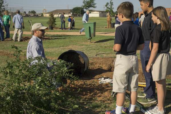 Mark Walter, with TreeKeepers, teaches Henderson Elementary fifth graders about planting a tree as they join forces with Keep Midland Beautiful, TreeKeepers and the City of Midland 04-20-17 to help plant 25 new trees in Henderson Park in celebration of Arbor Day 2017. Tim Fischer/Reporter-Telegram