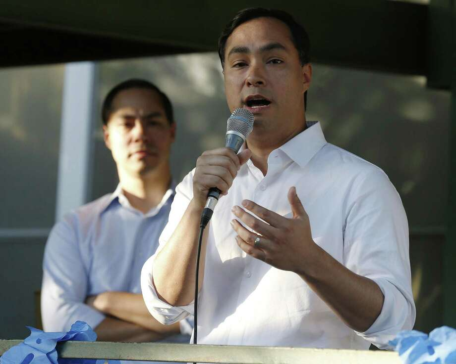 "Rep. Joaquin Castro (D-Texas) speaks at a ""Call to Action"" townhall rally as his twin sibling and former HUD Secretary Julian Castro (left) looks on at the event hosted by TX21 Indivisible where hundreds gathered to hear the Castros speak about the current state of political affairs in Texas and in the country on Wednesday, Apr. 19, 2017. Photo: Kin Man Hui, Staff / San Antonio Express-News / ©2017 San Antonio Express-News"
