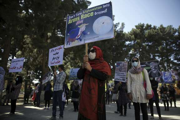 """Women from the Solidarity Party of Afghanistan hold posters during a demonstration against the U.S. government, in Kabul, Afghanistan, Sunday, April 16, 2017. Demonstrators protested against """"testing"""" """"Mother of all bombs"""" on an """"empty"""" village in eastern Nangarhar province, on Thursday, April 13. (AP Photo/Massoud Hossaini)"""