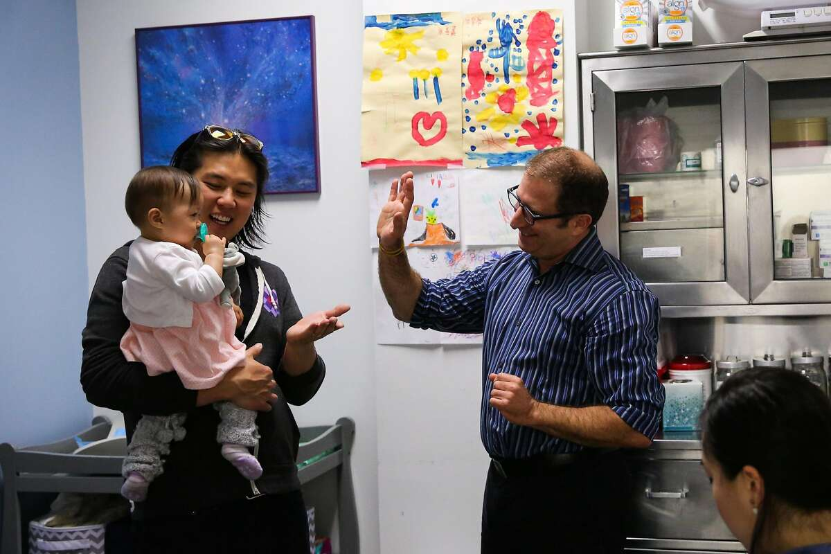 Dr. Oded Herbsman (center) gives Hazel Hua (left), 12 months, a high five after getting a vaccination with parents David Hua (left) and Stephanie Hua (right), in San Francisco, California, on Monday, April 17, 2017.