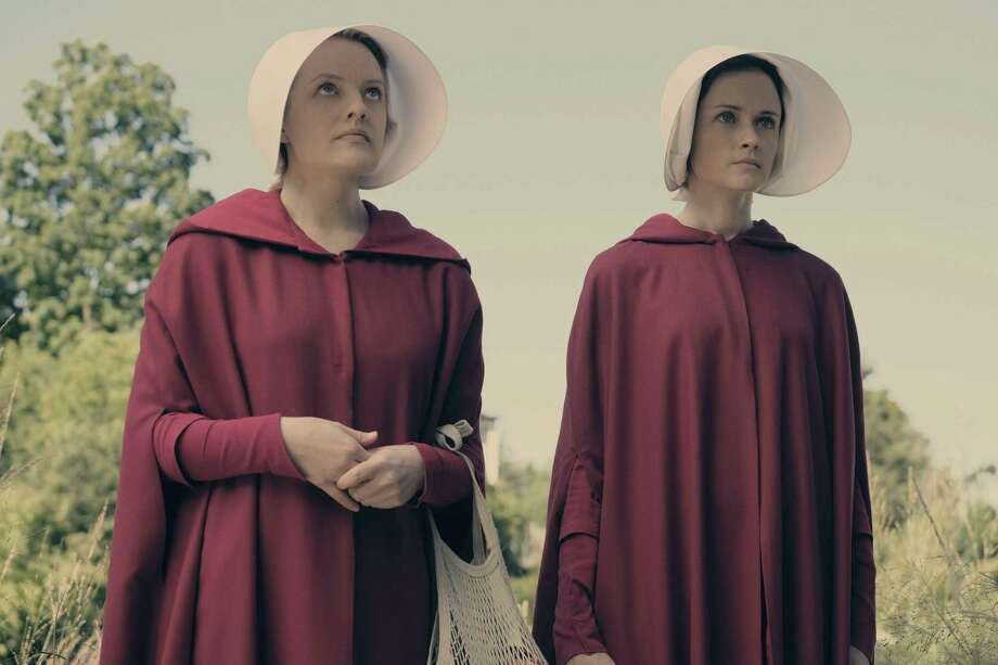 "Offred (Elizabeth Moss) and Ofglen (Alexis Bledel) are two of the women forced into sexual servitude by the state. Their purpose is to provided children to powerful men whose wives are infertile in ""The Handmaid's Tale,"" a disturbing dystopian drama on Hulu. Photo: George Kraychyk /Hulu / 2016 Hulu"