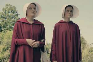 """Offred (Elizabeth Moss) and Ofglen (Alexis Bledel) are two of the women forced into sexual servitude by the state. Their purpose is to provided children to powerful men whose wives are infertile in """"The Handmaid's Tale,"""" a disturbing dystopian drama on Hulu."""