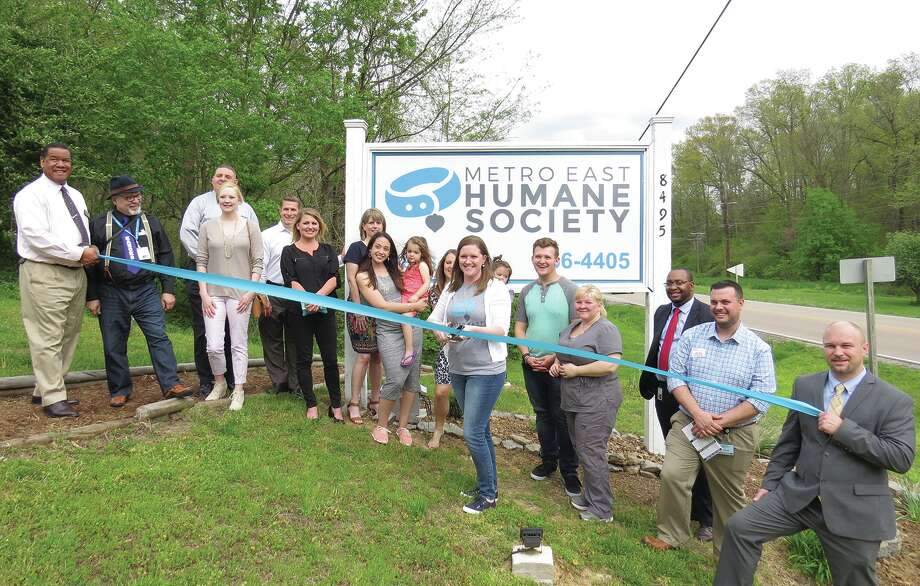 Metro East Humane Society Executive Director Anne Schmidt cuts the ribbon in front of the new sign at the society. The ribbon cutting marked the completion of three improvement projects at the shelter. The shelter will hold a Grand Re-opening celebration and open house this Sunday, April 23. from 11 a.m. to 3 p.m. Photo: Carol Arnett • Intelligencer