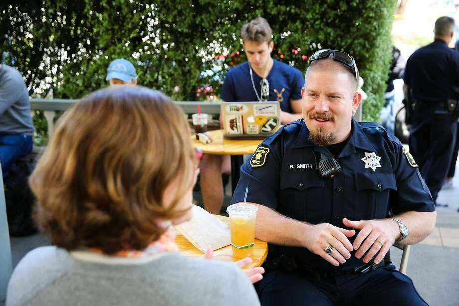 Berkeley police Officer Brandon Smith and Laura Novak chat during the department's community-engagement event at Caffe Strada. Photo: Gabrielle Lurie, The Chronicle