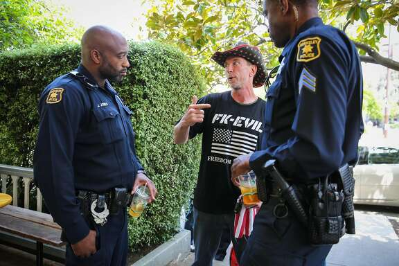 David Tomes (center) of Marin County chats with police sergeant Spencer Fomby (right) and Jumaane Jones (left) at Caffe Strada during a police community engagement event in Berkeley, California, on Wednesday, April 19, 2017.