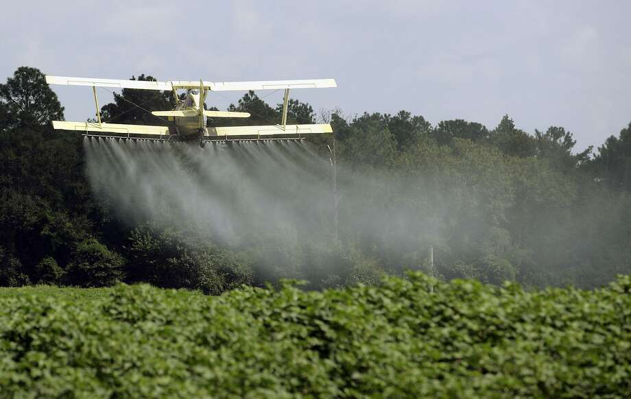 A crop duster sprays a field outside Headland, Ala., in 2009. Dow wants the EPA to scrap the findings that some pesticides harm endangered species. Photo: Dave Martin, Associated Press