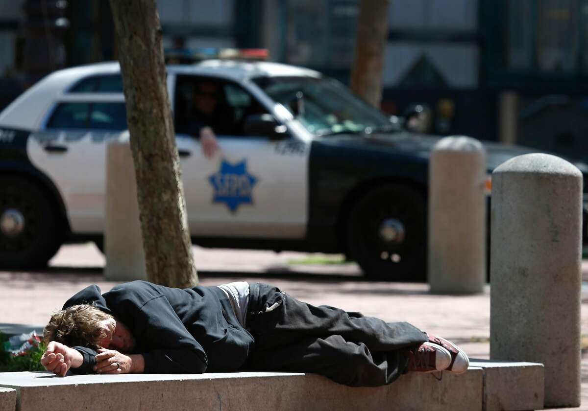 Police patrol at the edge of San Francisco's drug-riddled Tenderloin neighborhood at United Nations Plaza where a man is lying down. Drug overdoses have soared in the area especially during the past two years as fentanyl has become the opioid of choice.