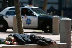 Police officers patrol in United Nations Plaza where a man is lying down, a common sight when people use drugs on the street in S.F. Officials hope a safe injection site will cut down on such public scenes.