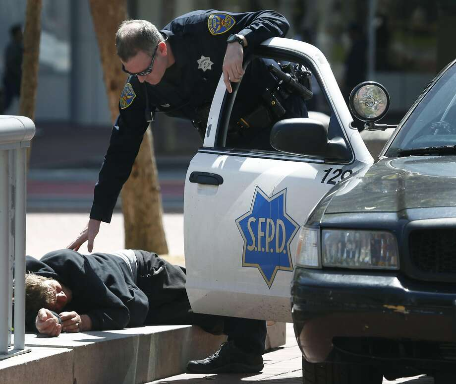 A police officer checks on the well being of a man lying down at United Nations Plaza in San Francisco, Calif. on Thursday, April 20, 2017. The city may soon become the first in the United States to open a safe injection site for intravenous drug users. Photo: Paul Chinn, The Chronicle