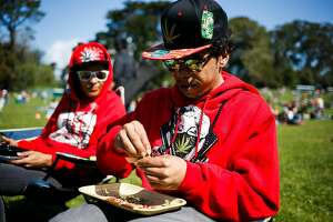 Marlon McKenzie, right, rolls a joint during the annual 4/20 celebration near Hippie Hill at Golden Gate Park in San Francisco, Calif. Thursday, April 20, 2017.