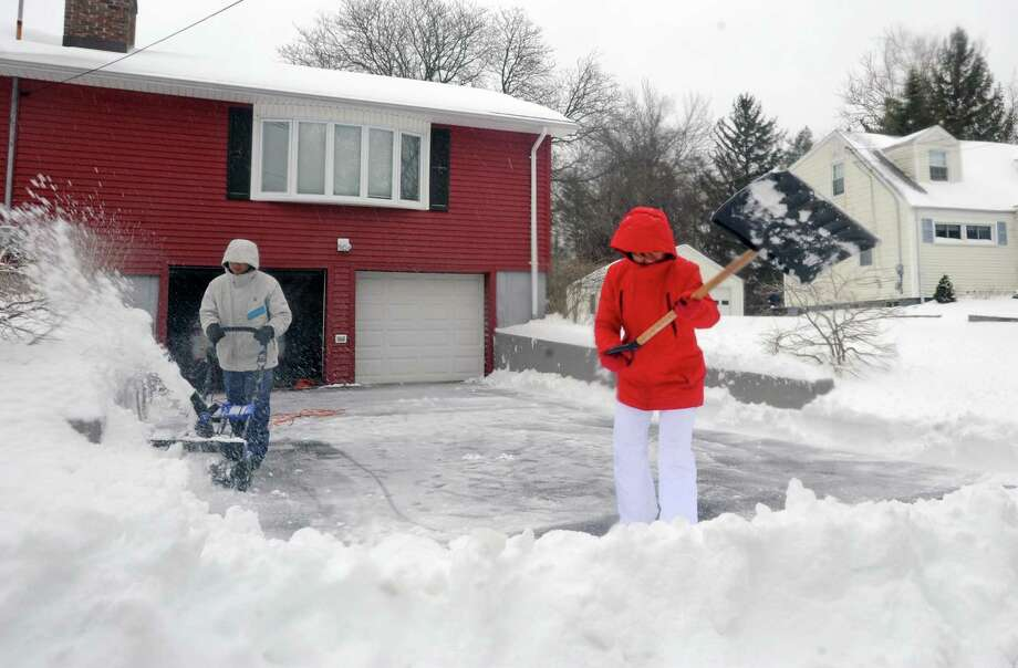 Nick Chen and Hui Tao clear the snow from their driveway on Mayfair Road in Fairfield on March 14. Photo: Cathy Zuraw / Hearst Connecticut Media / Connecticut Post