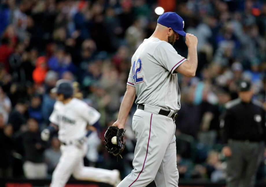Texas Rangers relief pitcher Mike Hauschild, right, turns away as Seattle Mariners' Taylor Motter rounds the bases behind on a three-run home run during the sixth inning of a baseball game Saturday, April 15, 2017, in Seattle. The Mariners won 5-0. (AP Photo/Elaine Thompson) Photo: Elaine Thompson, Associated Press / Copyright 2017 The Associated Press. All rights reserved.