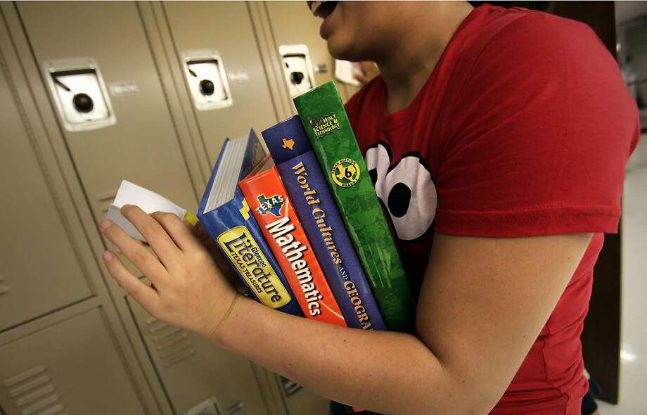 A a new student at Eisenhower Middle School prepares to put her textbooks in her locker. Eisenhower Middle School students, as well as other district's students, will be starting the school year without some of it's grammar textbooks. Friday, August 19, 2011. Photo Bob Owen/rowen@express-news.net Photo: BOB OWEN, SAN ANTONIO EXPRESS-NEWS