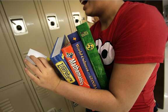 A a new student at Eisenhower Middle School prepares to put her textbooks in her locker. Eisenhower Middle School students, as well as other district's students, will be starting the school year without some of it's grammar textbooks. Friday, August 19, 2011. Photo Bob Owen/rowen@express-news.net