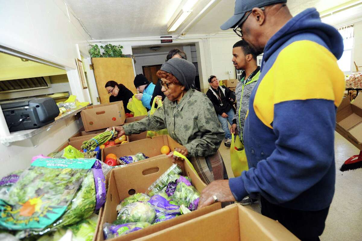 Mother Louise Montgomery, 92, grabs a bundle of asparagus to load into a bag at the Wilson Memorial Church in Stamford.