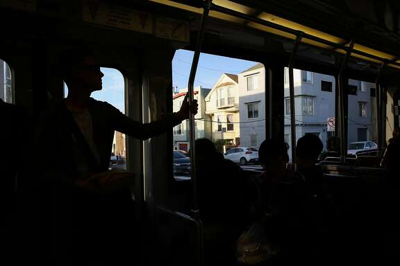 People are in silhoutte as houses in the Outer Sunset are seen from an N Muni bus in San Francisco, California, on Wednesday, April 19, 2017.