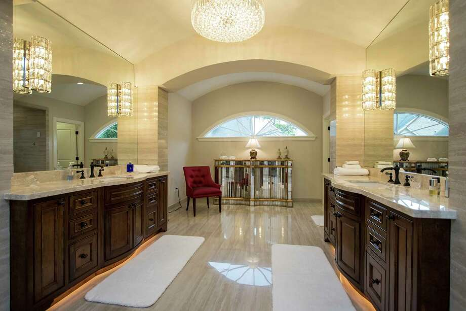 This elegant bathroom remodel shows layered lighting design. Photo: Courtesy Of Craftsmanship By John