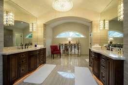 This elegant bathroom remodel shows layered lighting design.