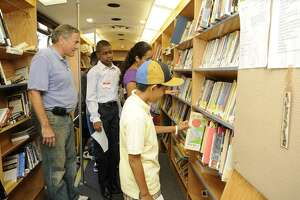 Joel Monge, 10, selects a book from the Bridgeport Public Library bookmobile which was part of a celebration for Bridgeport schoolchildren with perfect attendance. Schoolchildren with perfect attendance could invite a friend and were treated to a morning full of fun.