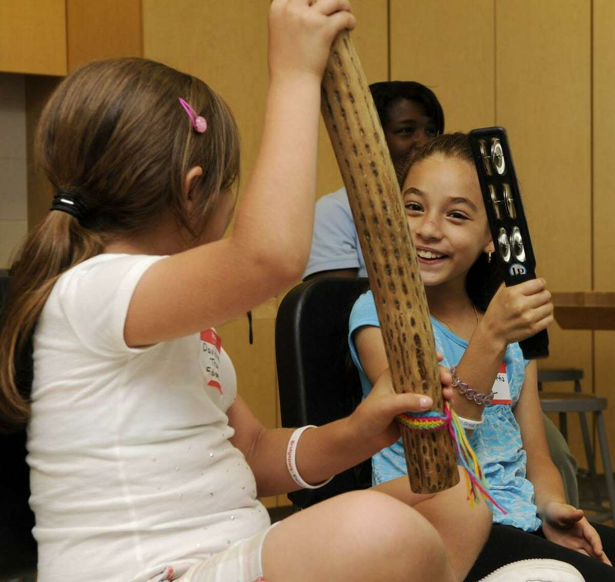 Davidianna Tracy (left) and Jessica Ortiz enjoy a music presentation at the Jettie Tisdale School in Bridgeport, CT on Friday August 20, 2010. Bridgeport schoolchildren with perfect attendance were treated to a morning full of fun.