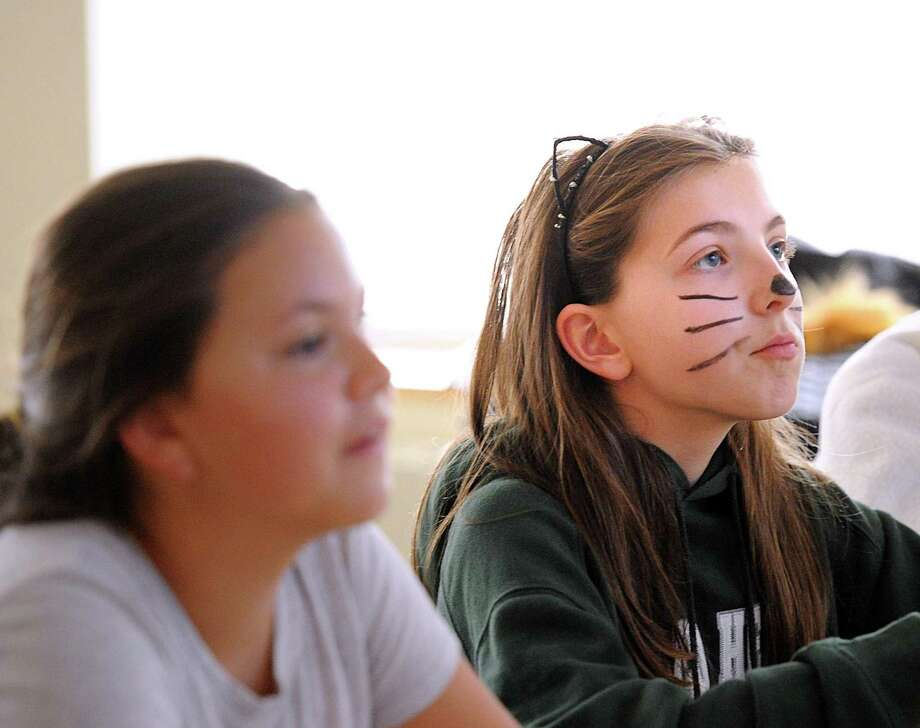 Sixth grade student Constanza Meyerhoff, 12, right, wore a cat costume to school as part of Earth Day activities at Sacred Heart Greenwich, Conn., Wednesday, April 19, 2017. Middle school students made a $3.00 donation for the privilege of wearing an animal costume to school and not having to wear their school uniform for the day. The money raised by the students was donated toward a clean water campaign for a Sacred Heart sister school in Uganda that they support. Photo: Bob Luckey Jr. / Hearst Connecticut Media / Greenwich Time