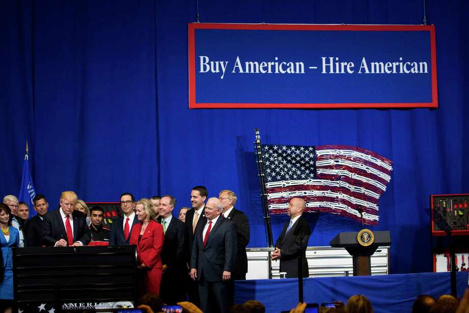 """President Donald Trump signs the é'Buy American, Hire Americané"""" executive order in Kenosha, Wis., April, 18, 2017. Trump spoke here as well. The order authorizes studies and tweaks in the rules that could lead to restrictions on high-skilled foreign workers. (Doug Mills/The New York Times) Photo: DOUG MILLS, STF / NYTNS"""