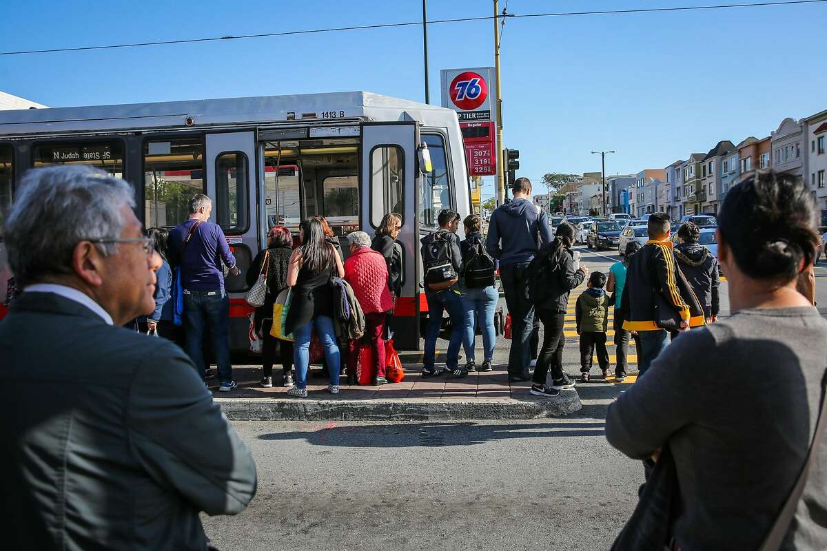 People gather along the sidewalk after disembarking from an N Muni train on Judah Street and 19th Avenue.