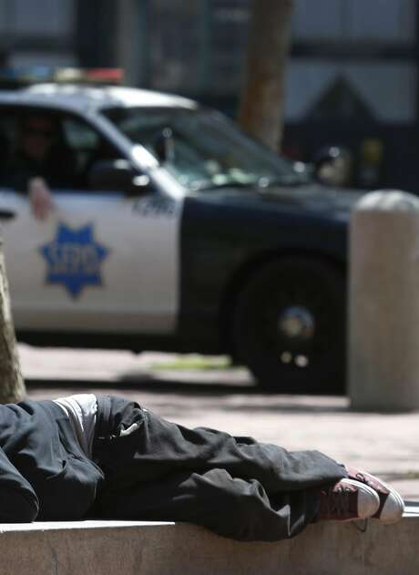 Officers patrol United Nations Plaza while a man lies on the concrete. Photo: Paul Chinn, The Chronicle