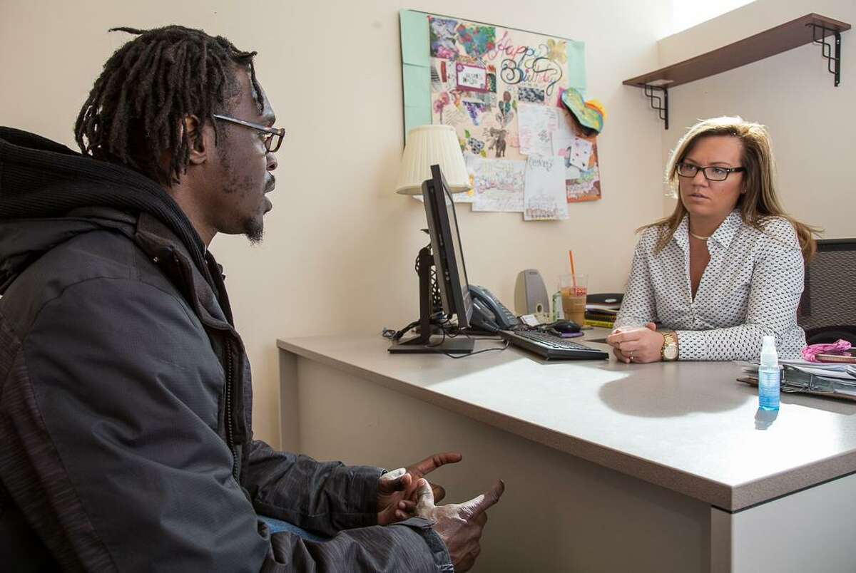 Chris Rhodes Sr., a Waterbury resident on special parole, speaks with clinician Casie Derosier at the Community Renewal Team's Hartford office for Re-Entry Recovery Services. CRT provides ex-offenders mental health and drug treatment services.